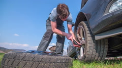 Man is putting the tier off of the car  - stock footage