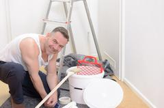 Muscular man doing DIY renovations Stock Photos