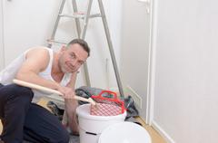 Muscular man doing DIY renovations - stock photo