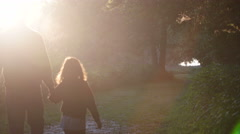 Father and daughter walking down trail at sunrise - stock footage