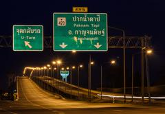 Stock Photo of Road signboard with bridge at night in Thailand