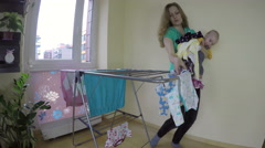 Mother with newborn baby on her hands pick up dry laundry. 4K Stock Footage