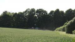Tractor spray fertilize wheat crop plant field near forest Stock Footage