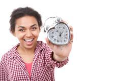 Smiling mulatto girl showing alarm clock - stock photo