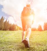 Man with backpack climb up to the  hill - stock photo
