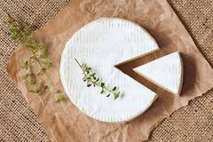 Stock Photo of Sliced round camembert cheese traditional milk creamy dairy product with thyme