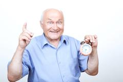 Upbeat grandfather holding alarm clock - stock photo