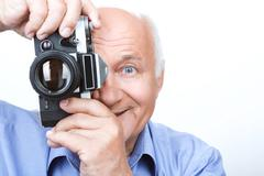 Vivacious grandfather holding camera Stock Photos