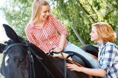 Stock Photo of Smiling girl sitting in the saddle