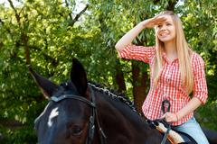 Girl looking ahead on the horse Stock Photos