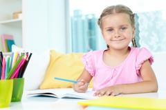 Girl with crayons Stock Photos