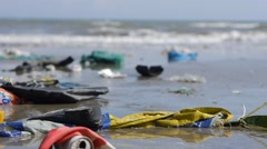 Handheld close up pan shot of trash and rubbish on seashore on sea background Stock Footage