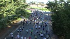 MASS OF RUNNERS TOWARDS CAMERA AND UNDER BRIDGE - SPORTFILM 10200R Stock Footage