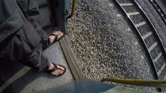 High angle view of human feet by open door of moving train. Stock Footage
