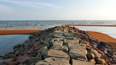 Calm beach from stone causeway at daylight - stock footage