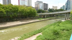 Green water of Sungai Kelang river, concrete banks and overgrown vegetation Stock Footage