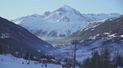 French Ski Resort Gondola with skiers and mountains in background - stock footage