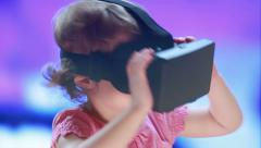Virtual reality game. The little girl with surprise uses head-mount display. - stock footage