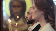 Close up wedding couple in a church with candles at Jesus Christ icon background Stock Footage