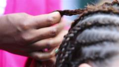 Traditional African braids. Woman braids hair girl on the street. - stock footage