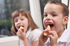 Sister and Brother Having Fun Eating an Apple - stock photo
