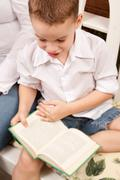 Cute Young Boy Reading His Book Indoors Next to His Mom. Stock Photos