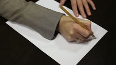 Woman writes in pencil on paper Stock Footage