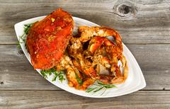 Spicy cooked crab ready to serve on white plate with rustic wood underneath - stock photo