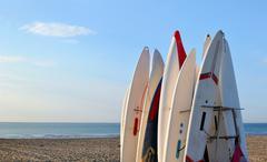 Surfboards awaiting fun in the sun on a beach - stock photo