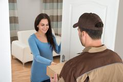 Smiling Young Woman Receiving Courier From Delivery Man At Home - stock photo