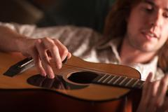 Young Musician Plays His Acoustic Guitar under Dramatic Lighting. - stock photo