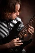 Young Musician Plays His Electric Guitar with Dramatic Lighting. - stock photo