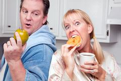 Couple in Kitchen Eating Donut and Coffee or Healthy Fruit. Stock Photos