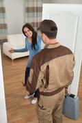 Happy Young Woman Welcoming Male Plumber At Home Stock Photos