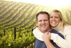 Happy Affectionate Couple Hugging at a Beautiful Wine Vineyard. - stock photo