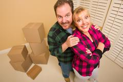 Proud Smiling Goofy Couple and Moving Boxes in Empty Room. - stock photo