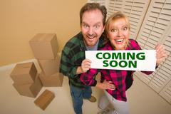 Goofy Couple Holding Coming Soon Sign in Room with Packed Cardboard Boxes. - stock photo
