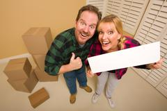 Goofy Thumbs Up Couple Holding Blank Sign in Room with Packed Cardboard Boxes - stock photo