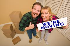 Goofy Couple Holding We're Moving Sign Surrounded by Boxes Stock Photos