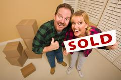 Goofy Thumbs Up Couple Holding Sold Sign in Room with Packed Cardboard Boxes. - stock photo