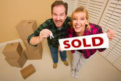 Goofy Couple Holding Key and Sold Sign in Room with Packed Cardboard Boxes. - stock photo