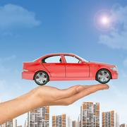 Red car above businesswomans hand with cityscape - stock photo