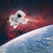 Astronaut in outer space with planet earth as backdrop. Elements of this imag - stock photo