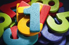 Bunch of wooden numbers, number one on top Stock Photos