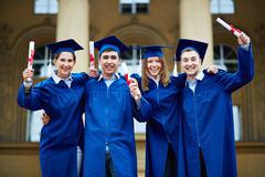 Graduates with certificates - stock photo