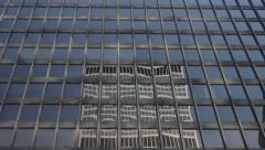 Pan down office building reflected in office building Stock Footage