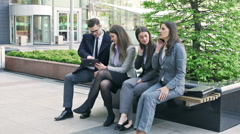 Businesspeople sitting on the bench and using electronics Stock Footage