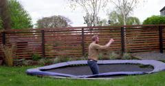 Handsome man does impressive back flip on trampoline in garden, Stock Footage