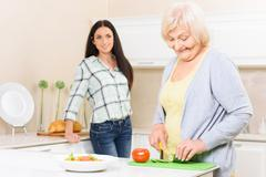 Granny cutting vegetables in kitchen - stock photo