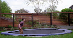 Young boy does flip on whilst trampolining in his garden Stock Footage